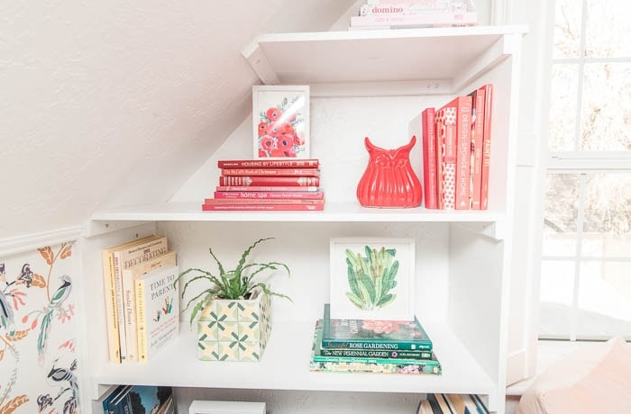 How to decorate shelves with colored-coordinated books stacked together on each shelf.