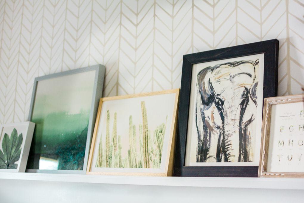 A long narrow wall shelf with framed art layered across it.