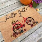 Doormat that reads hello fall picturing a bicycle and some flowers