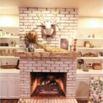 Fireplace and mantel with fall decor including candles and deer head with grapevine wreath.