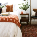 Fall Bedroom Decor - Fall inspired bedroom setting with a cozy orange blanket at the foot of the bed and orange throw pillows and an orange candle on the bedside table.