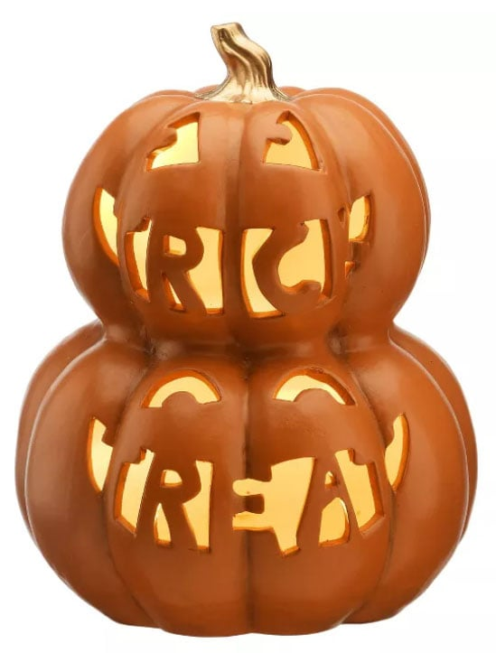 Double stacked orange pumpkin jack o lantern with the works trick or treat carved in.