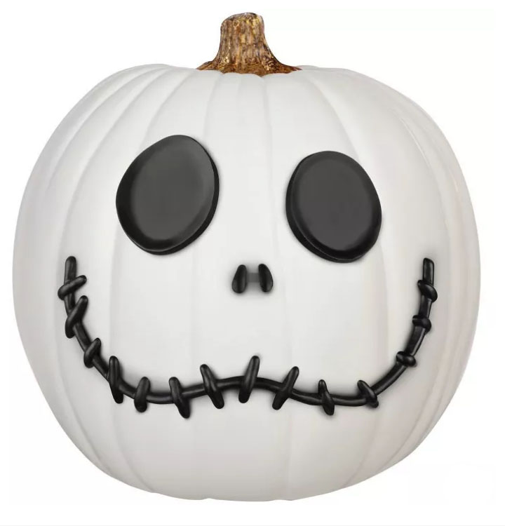 White pumpkin with black eyes, nose, and smile