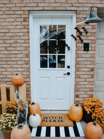 Front door decorated for halloween. White door with a black wreath, bats and spider webs. Orange and white pumpkins along with orange and yellow colored mums on a black and white striped doormat and another doormat layered that reads witch please.