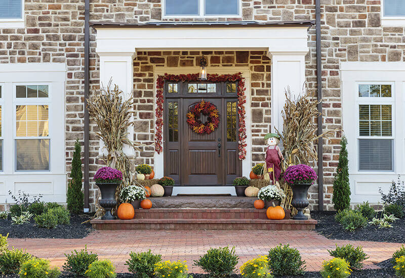 Front door and porch decorated for the fall with a leaf wreath on the door and corn stalks with purple colored mum flowers and orange pumpkins.