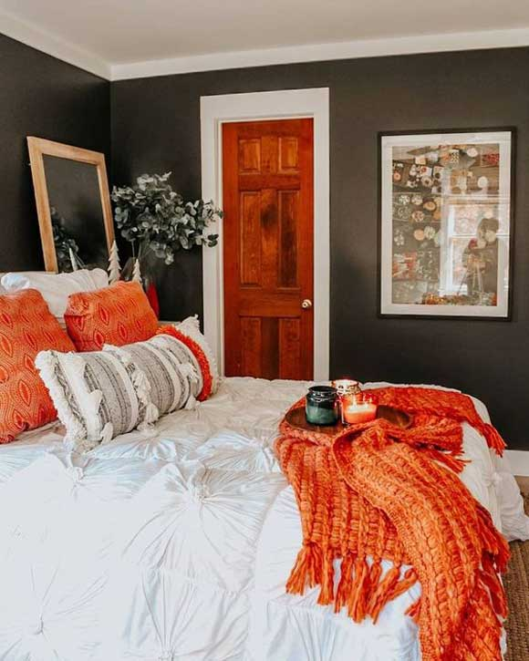 Bedroom with black walls and a bed with white bedding and orange colored pillows and a orange throw blanket and  orange and green candles.