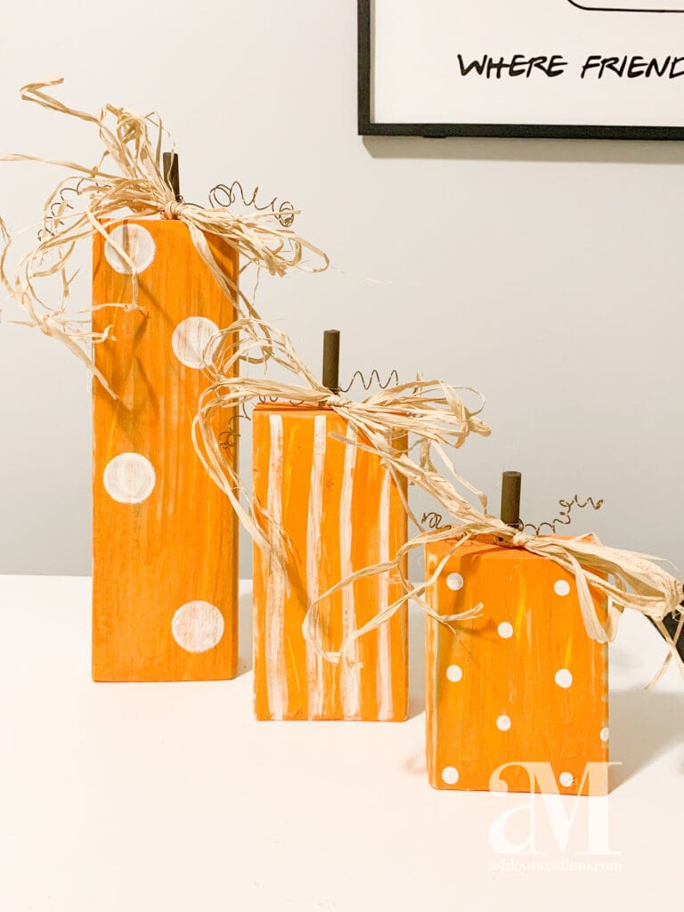 Three different sized wood blocks painted orange as pumpkins with polka dots, and stripes.