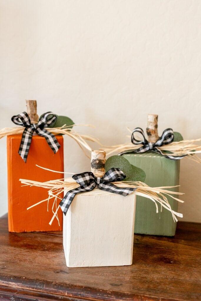 Three wood blocks painted as pumpkins, orange, white and green.