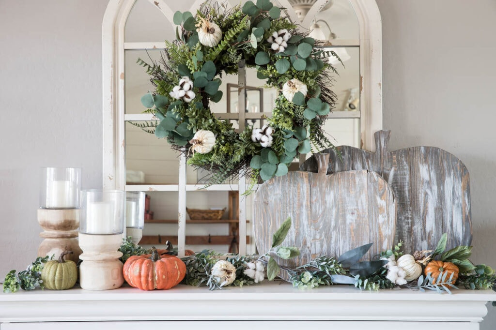 Mantel with two rustic wood pumpkins, candles and some greenery and other small pumpkins.