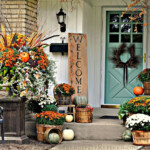 Front door and porch area decorated for the fall with pumpkins and brightly colored fall leaves and flowers with a welcome sign.