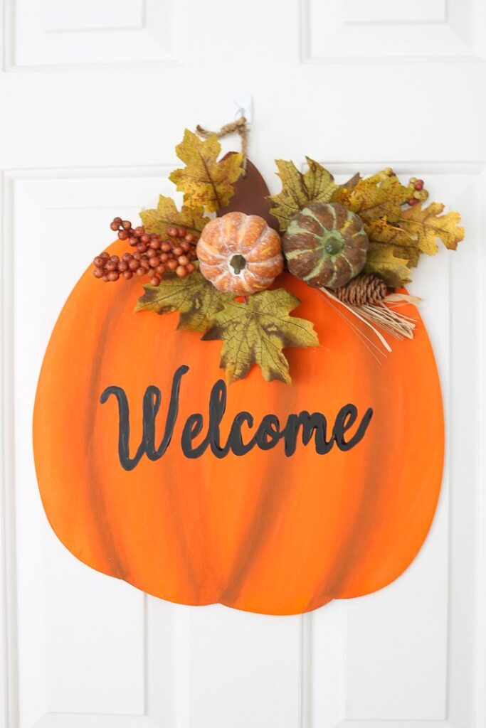 Orange wood cut out in the shape of a pumpkin that has the word welcome painted on it.