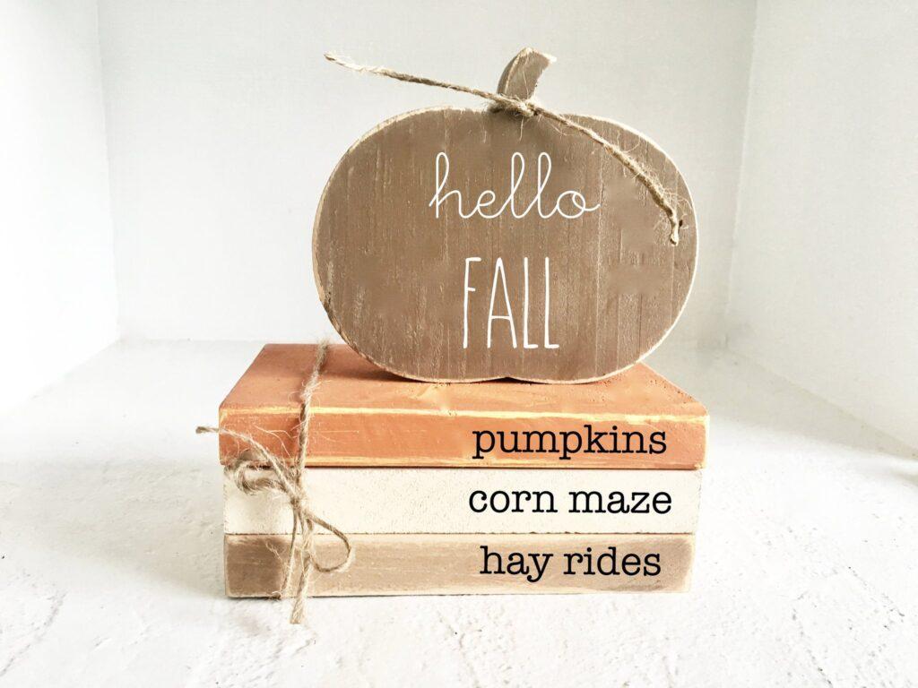 Wood pumpkin and wood book stack.
