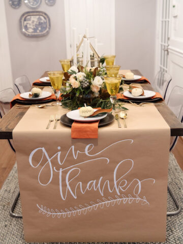 Thanksgiving table set with butcher paper with the words Give Thanks written on it.