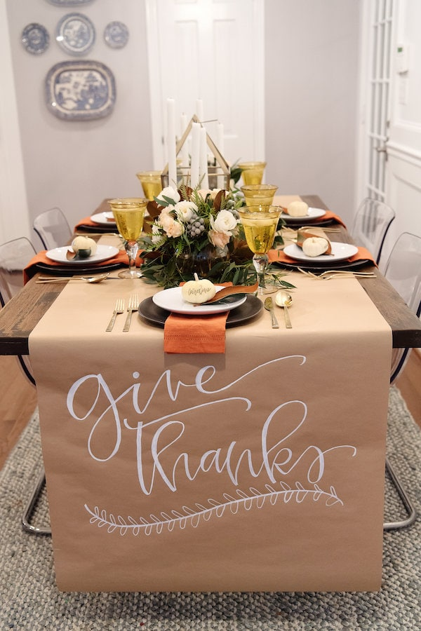 craft paper rolled out across wooden table with the words give thanks handwritten on it
