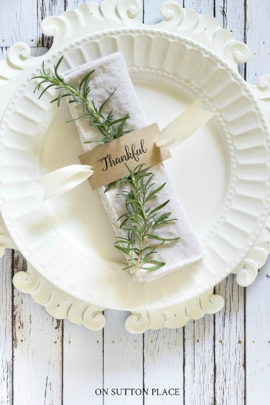 white place on a white charger with a cloth napkin rolled up with dried herbs and a name plate for thanksgiving table decor